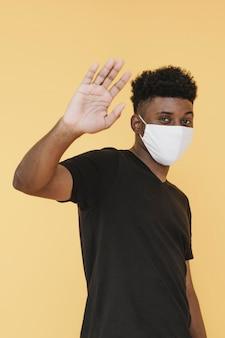 Vista lateral del hombre con mascarilla levantando la mano