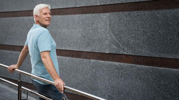 Vista lateral, de, hombre mayor, posar, aire libre