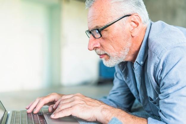 Vista lateral del hombre mayor que usa la computadora portátil