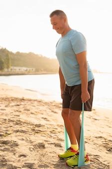 Vista lateral del hombre mayor trabajando con cuerda elástica en la playa