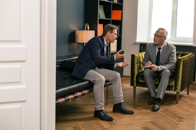 Vista lateral de un hombre de mediana edad preocupado hablando con su psicoterapeuta atento mientras está sentado en su oficina