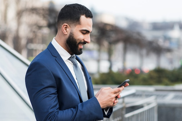 Vista lateral hombre mirando móvil