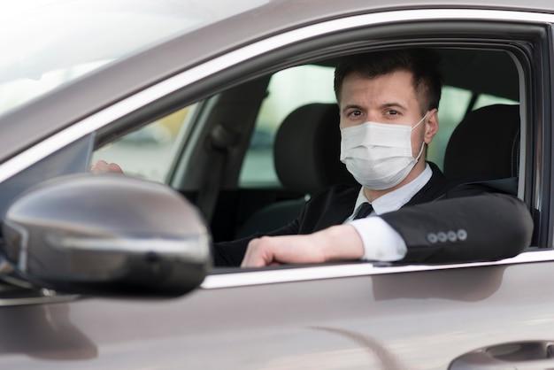 Vista lateral hombre moderno en coche con máscara