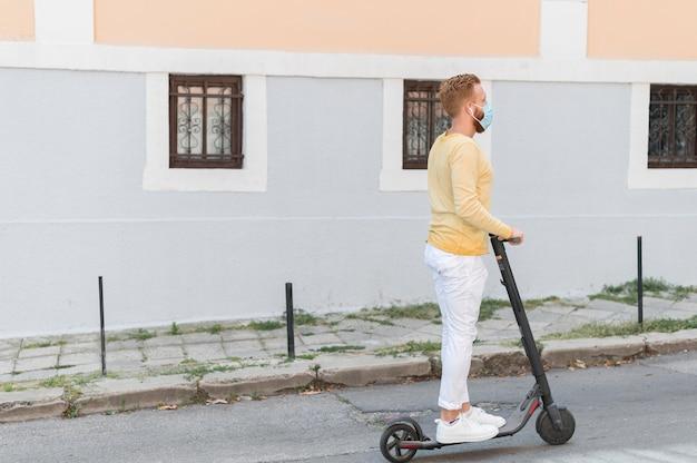 Vista lateral del hombre moderno montando su scooter con espacio de copia