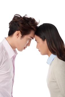 Vista lateral del hombre y la mujer apoyando la frente uno contra el otro, concepto de competencia y confrontación