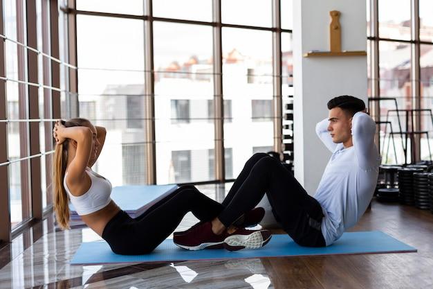 Vista lateral del hombre y la mujer haciendo abdominales