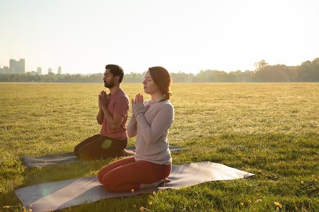 Vista lateral del hombre y la mujer meditando al aire libre sobre esteras de yoga