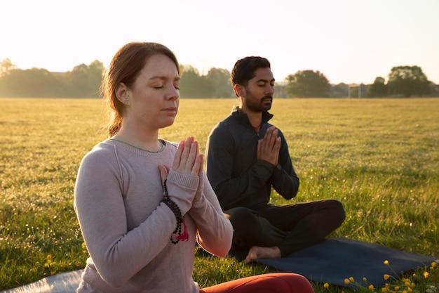 Vista lateral, de, hombre y mujer, meditar, aire libre