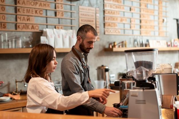 Vista lateral del hombre y la mujer que trabaja en la cafetería.