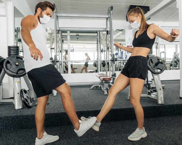 Vista lateral del hombre y la mujer saludando con los pies en el gimnasio