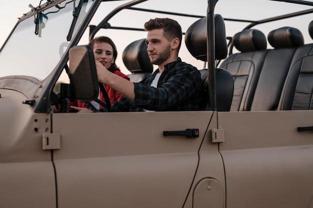 Vista lateral, de, hombre y mujer, viajar, en coche