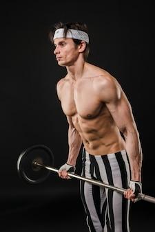 Vista lateral del hombre musculoso sin camisa levantando pesas
