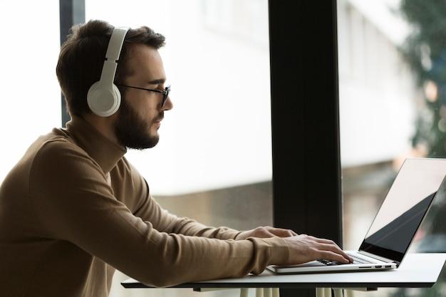 Vista lateral hombre de negocios con auriculares trabajando