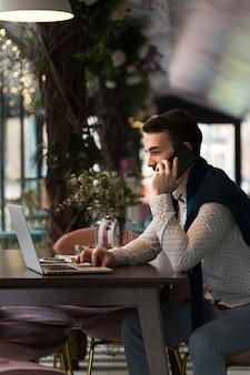 Vista lateral hombre de negocios hablando en el teléfono