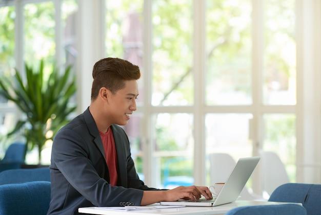 Vista lateral del hombre ocupado escribiendo en el teclado del portátil con una sonrisa