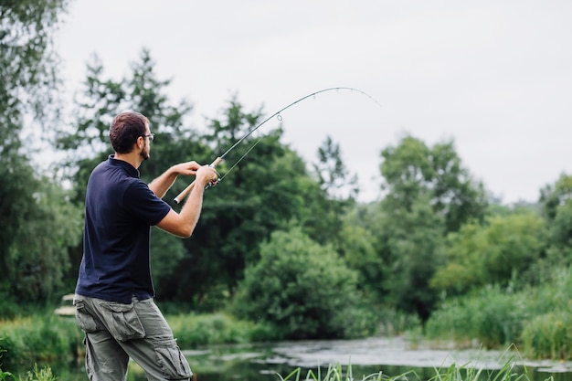 Vista lateral del hombre pescando en el lago