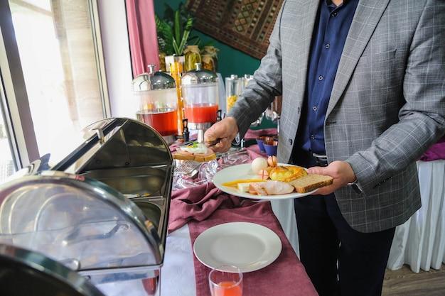 Vista lateral hombre pone comida de desayuno salchichas de huevo pan tostado y queso en un plato del buffet abierto