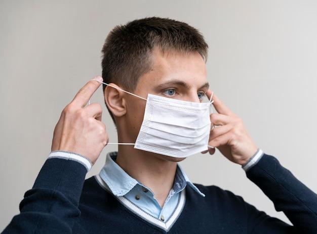 Vista lateral del hombre poniéndose mascarilla médica