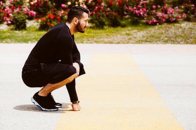 Vista lateral de un hombre en posición de listo para correr