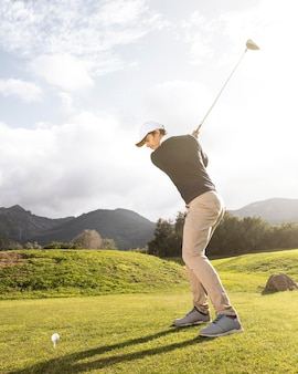 Vista lateral del hombre practicando golf en el campo