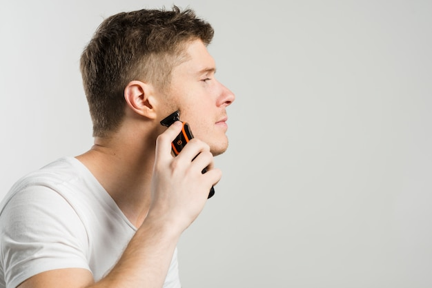 Vista lateral de un hombre que afeita rastrojo con una maquinilla de afeitar eléctrica aislada sobre fondo gris