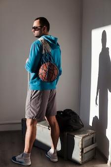 Vista lateral del hombre que llevaba gafas de sol con baloncesto en red