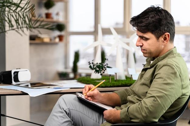 Vista lateral del hombre que trabaja en un proyecto de energía eólica ecológica con portapapeles