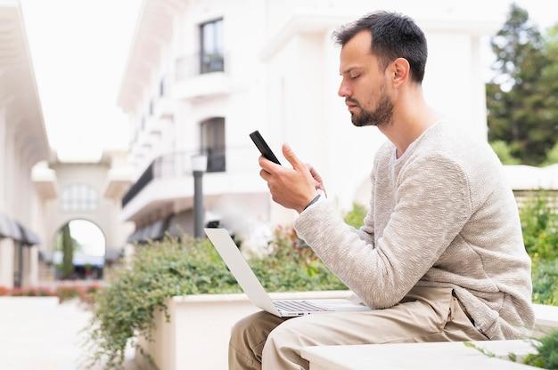 Vista lateral del hombre que trabaja en teléfonos inteligentes y portátiles al aire libre