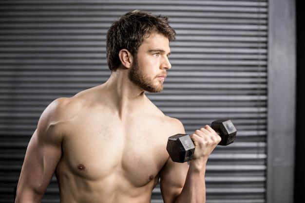 Vista lateral del hombre serio que levanta el peso en el gimnasio
