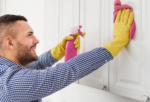 Vista lateral del hombre sonriente limpieza de armarios de cocina
