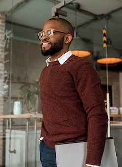 Vista lateral del hombre sonriente sosteniendo una computadora portátil