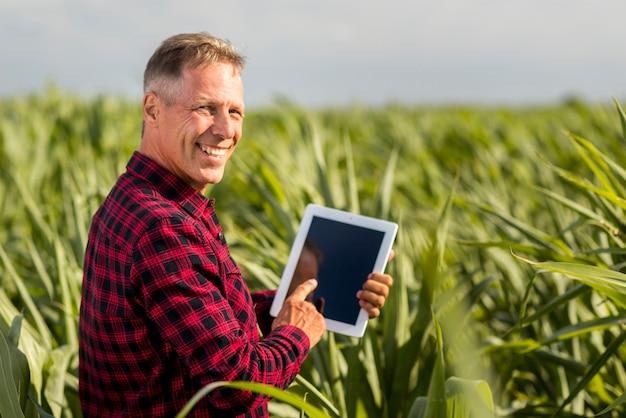 Vista lateral del hombre con una tableta en una maqueta de campo de maíz