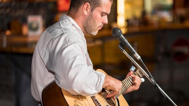 Vista lateral del hombre tocando la guitarra en un bar.