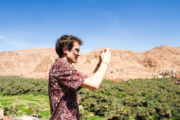 Vista lateral de un hombre tomando foto de oasis.