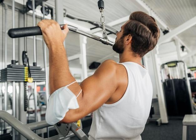 Vista lateral del hombre trabajando en el gimnasio con máscara médica en su antebrazo