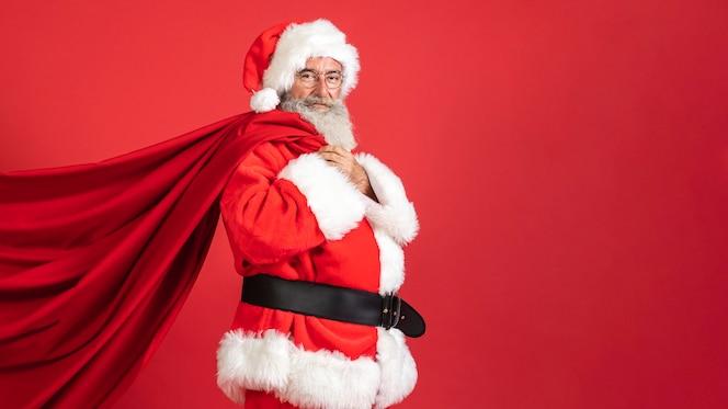 Vista lateral del hombre en traje de santa con bolsa de regalo con espacio de copia