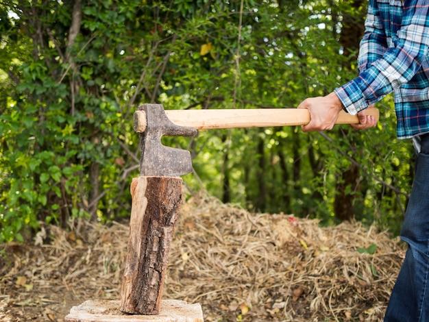 Vista lateral hombre usando un hacha para cortar madera