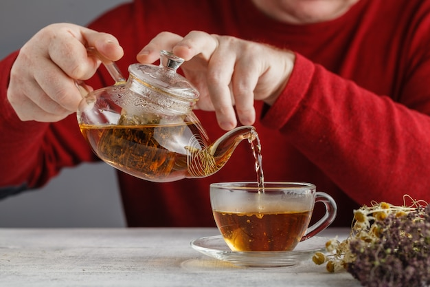 Vista lateral de un hombre vertiendo té