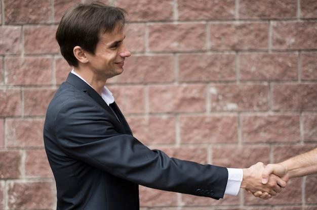 Vista lateral de hombres dándose la mano
