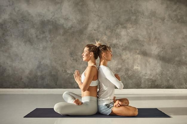 Vista lateral horizontal de la atractiva pareja joven practicando yoga juntos en el interior. hombre y mujer caucásicos pacíficos sentados espalda con espalda en posición de loto, tomados de la mano en namaste, manteniendo los ojos cerrados