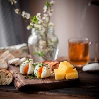 Vista lateral de huevo escalfado con taza de té y queso y flores en frasco en utensilios de cocina en mesa de madera