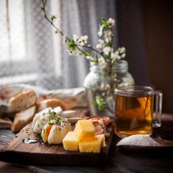 Vista lateral del huevo escalfado con taza de té y queso y flores en frasco en utensilios de cocina