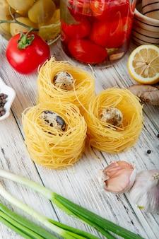 Vista lateral de huevos rodeados de fideos con tomate cebolleta ajo y limón cortado sobre fondo de madera