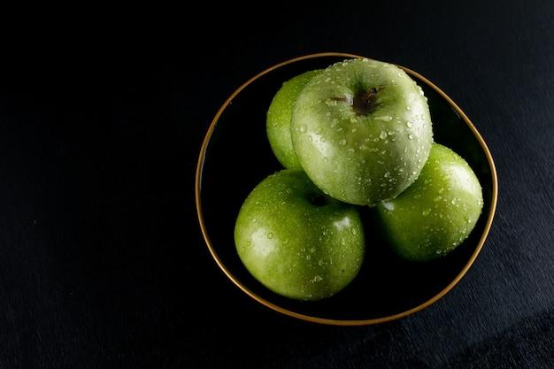 Vista lateral húmedas manzanas verdes en un tazón