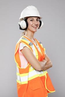 Vista lateral de la ingeniera sonriente con casco