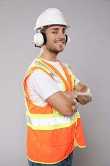 Vista lateral del ingeniero hombre sonriente con casco