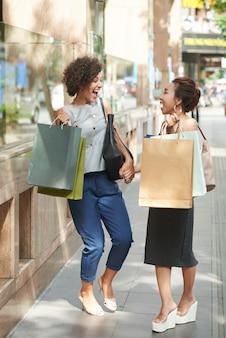 Vista lateral integral de novias riendo a carcajadas con bolsas de compras en la calle