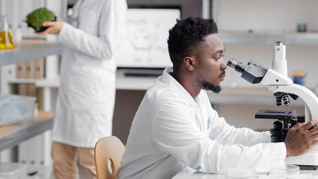 Vista lateral del investigador masculino en el laboratorio con microscopio