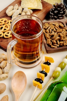 Vista lateral de una jarra de cerveza con varios bocadillos salados sobre la mesa