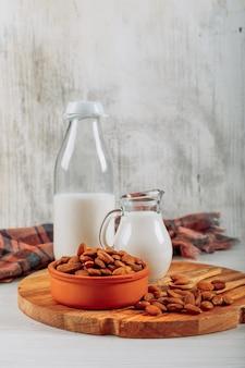 Vista lateral jarra de leche y botella con tazón de almendras sobre tabla de madera sobre fondo blanco de madera. horizontal